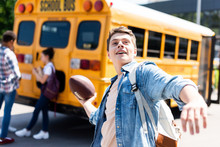Smiling Teen Schoolboy Throwing American Football Ball In Front Of School Bus