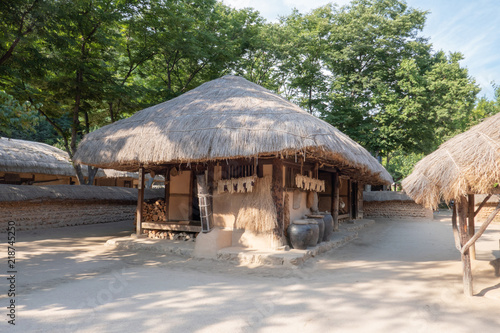 Traditional Korean house with thatched roof and kimchi pots
