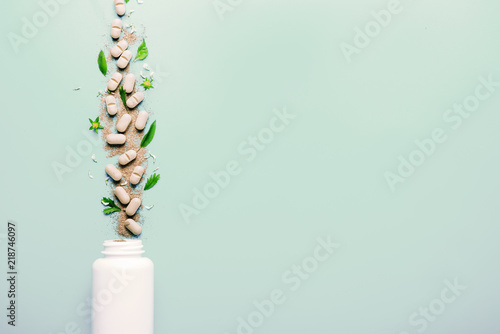 Fotografia  Natural herbal additives from herbs, poured from a white jar