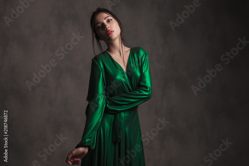 Wallpaper Mural portrait of young woman in green dress leaning to side