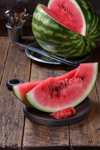 Sliced ripe watermelon on brown wooden table.