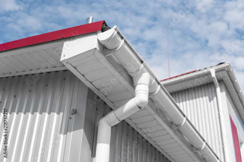 White guttering on a home with red roof against blue sky Canvas-taulu