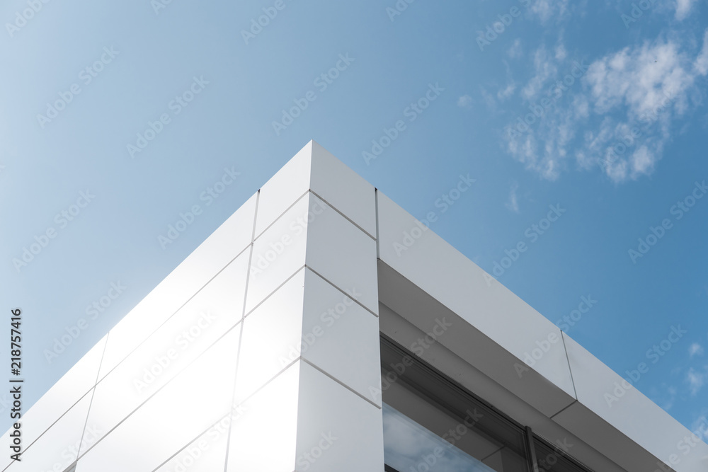 Fototapeta Building with white aluminum facade and aluminum panels against blue sky.