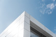 canvas print picture - Building with white aluminum facade and aluminum panels against blue sky.