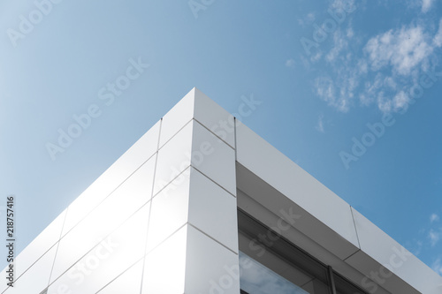 Building with white aluminum facade and aluminum panels against blue sky. - fototapety na wymiar