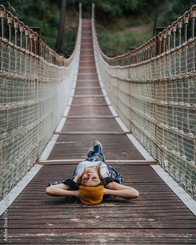 Canvastavla Woman laying on back on footbridge