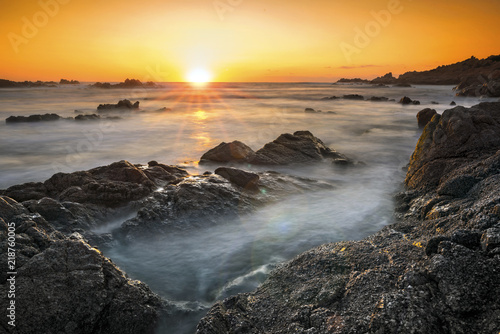 Romantic sunset over rocky coast and soft silky water