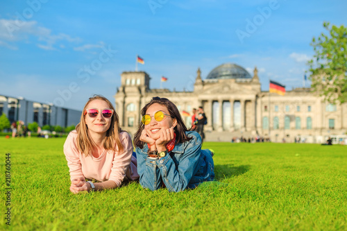 Two Young happy girls wearing sun glasses lying on a grass and have fun in front of the Bundestag building in Berlin Wallpaper Mural