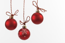 Hanging Red Christmas Baubles On White Background