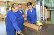 carpentry apprentices using a band saw