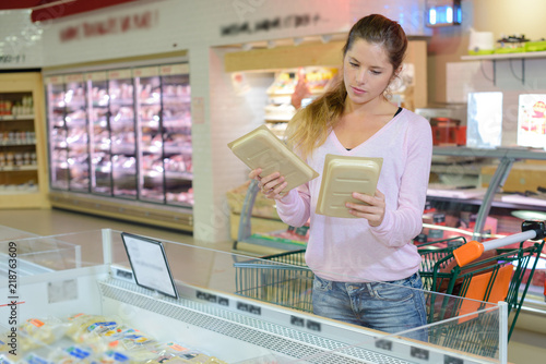 Plakat Kobieta w supermarkecie porównanie dwóch paczek żywności