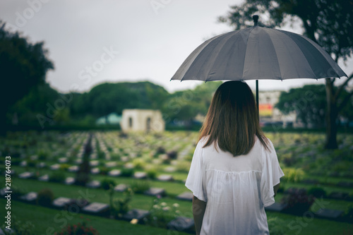 Photo  Young woman holding black umbrella mourning at cemetery