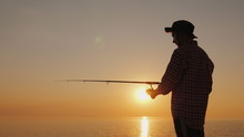 Silhouette Of A Young Fisherman Fishing On The Beach At Sunset. Side View