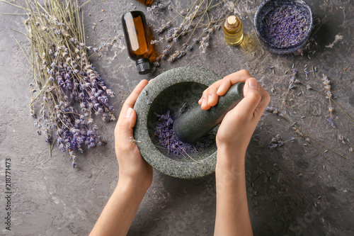 Fotomural Woman grinding lavender flowers in mortar, top view