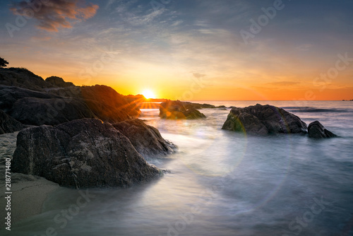 Romantic sunset over sandy beach and soft silky water