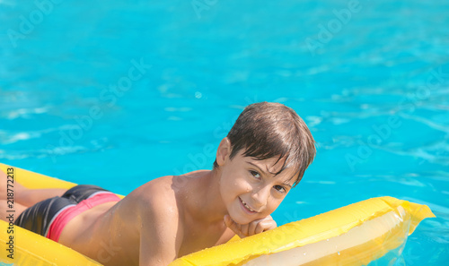 Cute boy on inflatable mattress in swimming pool on summer day