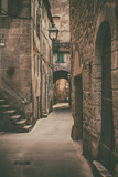 Fototapeta  - Narrow street of medieval ancient tuff city Pitigliano, travel Italy background