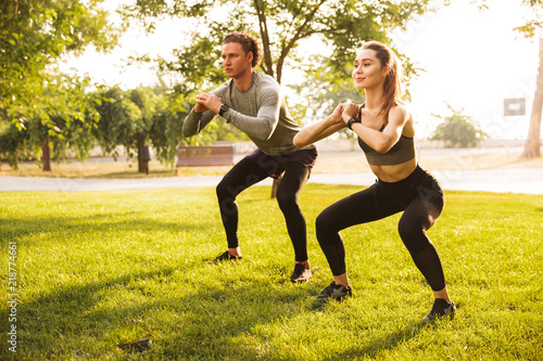 Image of young caucasian sporty man and woman 20s in tracksuits, doing workout a Fototapet