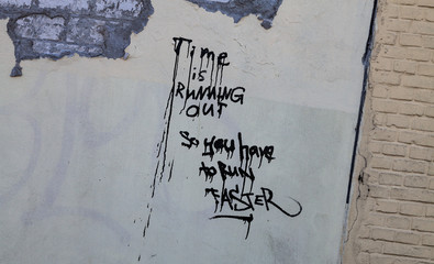 Time is running out graffito on a grey wall