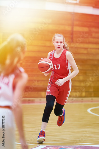Girl basketball player with ball in game