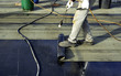 canvas print picture - Worker preparing part of bitumen roofing felt roll for melting by gas heater torch flame