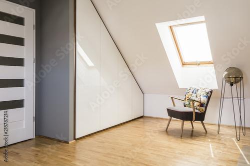 Fototapeta Lamp next to armchair on wooden floor in white attic interior with door and window