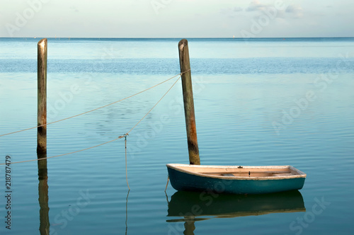 Photo  Solitary small boat moored at soft blue sunrise in the Florida Keys
