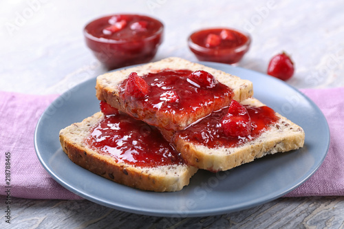 Plate with slices of bread and delicious strawberry jam on light wooden table, closeup