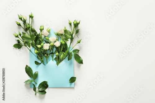 Fotografía  Open mail envelope with rose flowers on white background