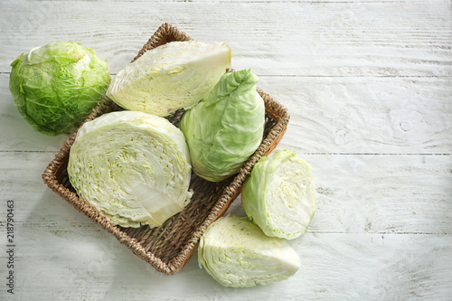 Wicker basket with fresh cabbage on white table Poster Mural XXL