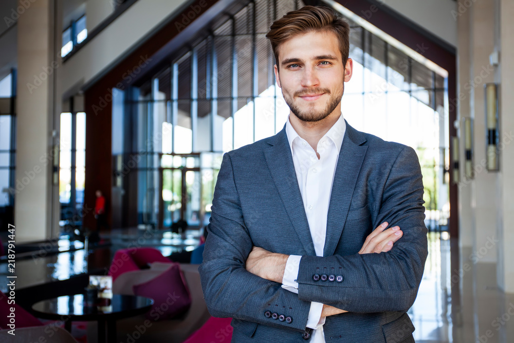 Fototapeta Portrait of happy businessman with arms crossed standing in office.