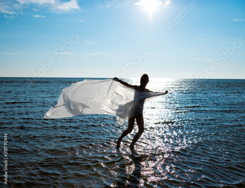 Tuinposter Akt Young naked woman wrapped in white shawl posing at the beach