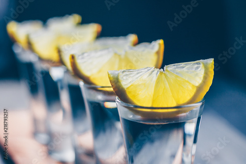 Fotografía  Close-up of selective focus on a row of wine glasses with vodka and lemon on the