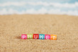 Word PHUKET from multicolored cubes in the sand on the background of beach and sea