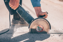 The Worker Saws The Asphalt With An Angular Grinder With A Diamond Disc Before Carrying Out Repair And Repair Work