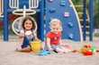 Leinwandbild Motiv Happy childhood. Two cute Caucasian and hispanic latin babies children sitting in sandbox playing with plastic colorful toys. Little girls friends having fun together on playground.
