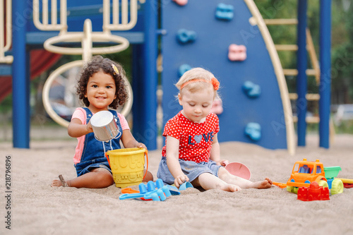 Obraz Happy childhood. Two cute Caucasian and hispanic latin babies children sitting in sandbox playing with plastic colorful toys. Little girls friends having fun together on playground. - fototapety do salonu