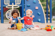 Sandy Ground. Two Cute Caucasian And Hispanic Latin Babies Children Sitting In Sandbox Playing With Plastic Colorful Toys. Little Girls Friends Having Fun Together On Playground.