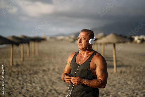 Elderly man listens to music on the beach.