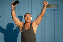 Strong Older Man Poses With Headphones On Blue Cabin Background.