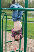 Young Boy With Gastric G-tube Hanging Upside Down From Monkey Bars On Jungle Gym Playground At Park.