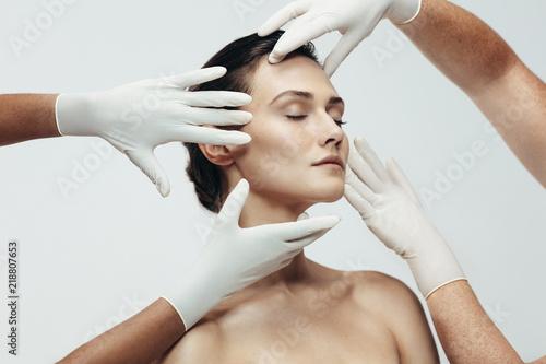 Obraz na plátně  Cosmetologists examining facial skin of female