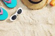 Some Beach accessories. hat ,Sandals slippers,sunglasses,sunblock lotion on the sandy shore on the summer sands of the sea. with copy space on the below side. Concept of travel summer vacations sea.