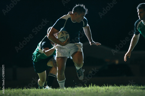 Flanker with ball tackling during game