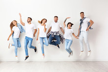 Group Of Young People In Jeans Jumping Near Light Wall
