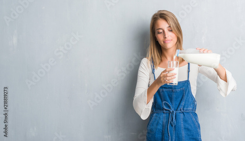 Fényképezés  Beautiful young woman over grunge grey wall driking a glass of milk with a confi