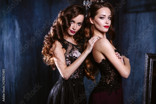 Twins young women in evening dresses, fashion beauty portrait in dark interior Wallpaper Mural