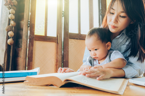 Valokuva  Business woman teaching her child about investment with multimedia and book, home school education