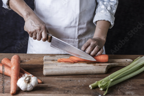 Fotografie, Obraz  Slicing carrots on a cutting board.
