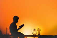 Boy Reading Bible With Oil Lamp And Sunset Background.christian Concept